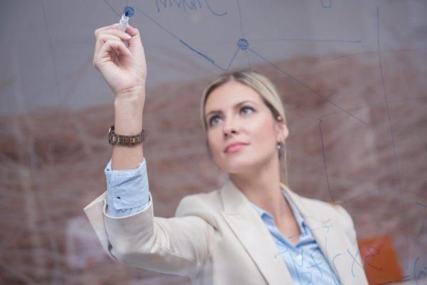 woman writing on glass board